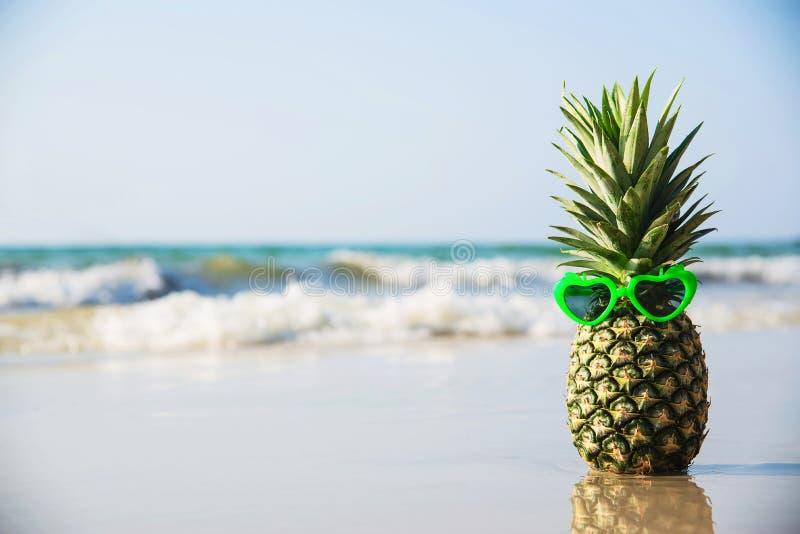 Uroczy świeży ananas stawiający kierowi kształta słońca szkła na czystej piasek plaży z morzem machają tło zdjęcia royalty free