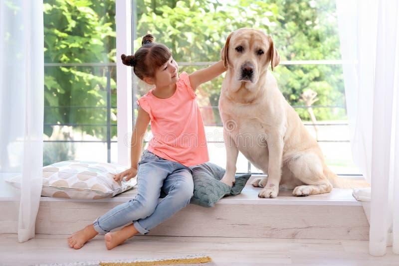 Uroczy żółty Labrador retriever i mała dziewczynka fotografia royalty free