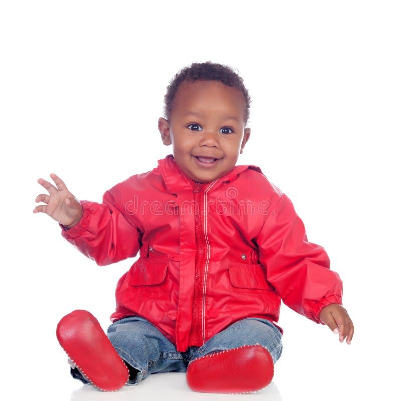 Uroczy afrykański dziecka obsiadanie na podłoga z czerwonym deszczowem obrazy stock