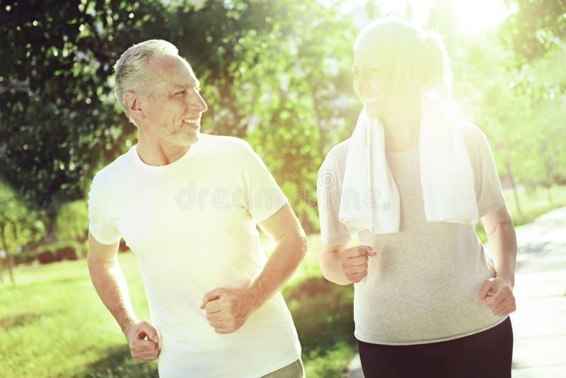 Uroczy aktywni starsi ludzie biega w parku obrazy royalty free