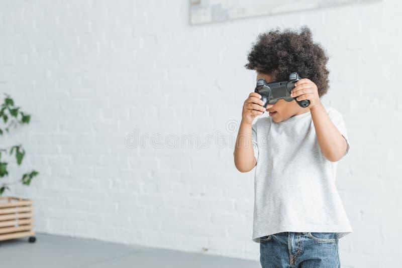 uroczy amerykanin afrykańskiego pochodzenia chłopiec mienia gamepad fotografia royalty free