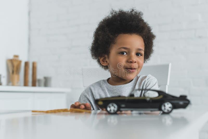 uroczy amerykanin afrykańskiego pochodzenia chłopiec obsiadanie przy stołem z samochód zabawką i patrzeć kamerę obrazy royalty free