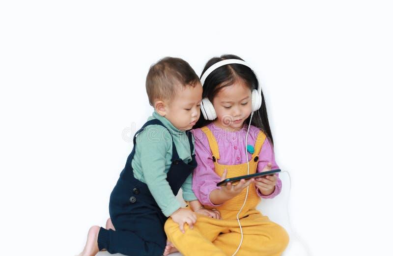 Uroczy Azjatycki stary siostry i m?odszego brata udzielenie cieszy si? s?uchaj?c? muzyk? z he?mofonami smartphone odizolowywaj?cy zdjęcie royalty free