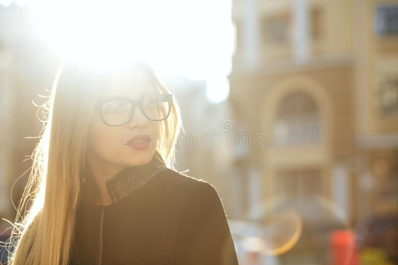 Uroczy blondynka model jest ubranym szkła i odprowadzenie puszka pogodną ulicę Opróżnia przestrzeń zdjęcia stock