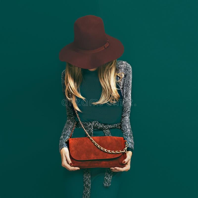 Uroczy blondyny modelują w modnym czerwonym kapeluszu i czerwieni sprzęgle na gr zdjęcia stock