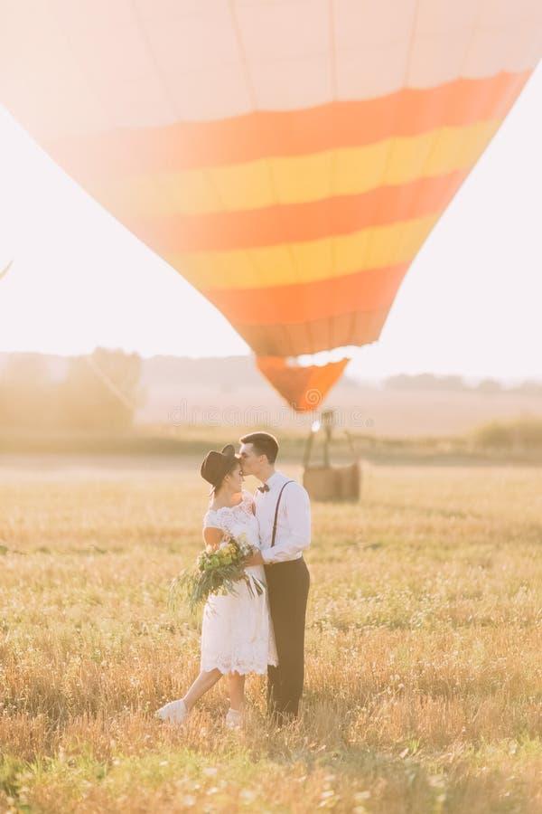 Uroczy boczny portret szczęśliwi nowożeńcy w pogodnym polu Fornal całuje panny młodej w jej czoło w fotografia royalty free