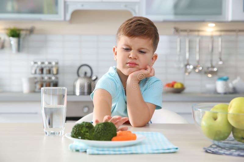 Uroczy chłopiec odmawianie jeść warzywa przy stołem zdjęcie royalty free