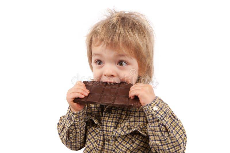 Uroczy dwa lat dziecko je czekoladowego baru Odizolowywający dalej zdjęcie royalty free