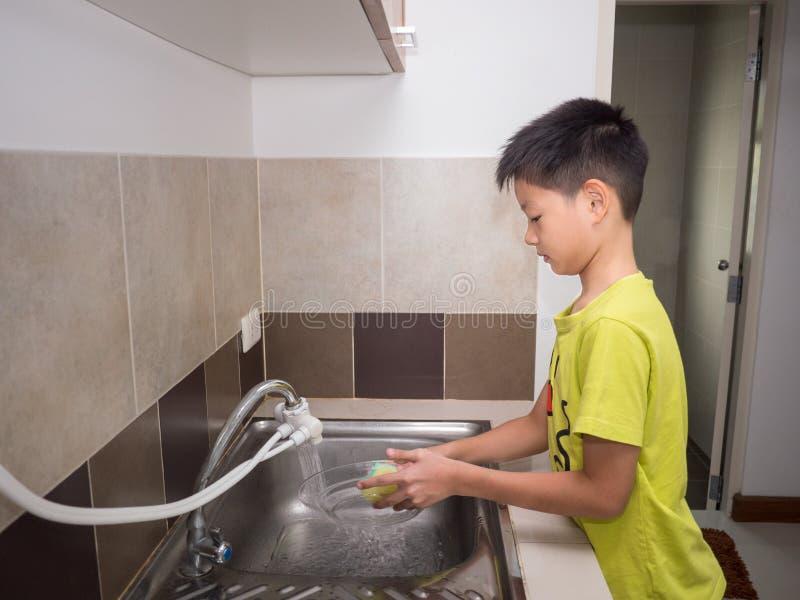 Uroczy dzieciak chłopiec domycia naczynia w domowej kuchni Dziecka havi obrazy stock