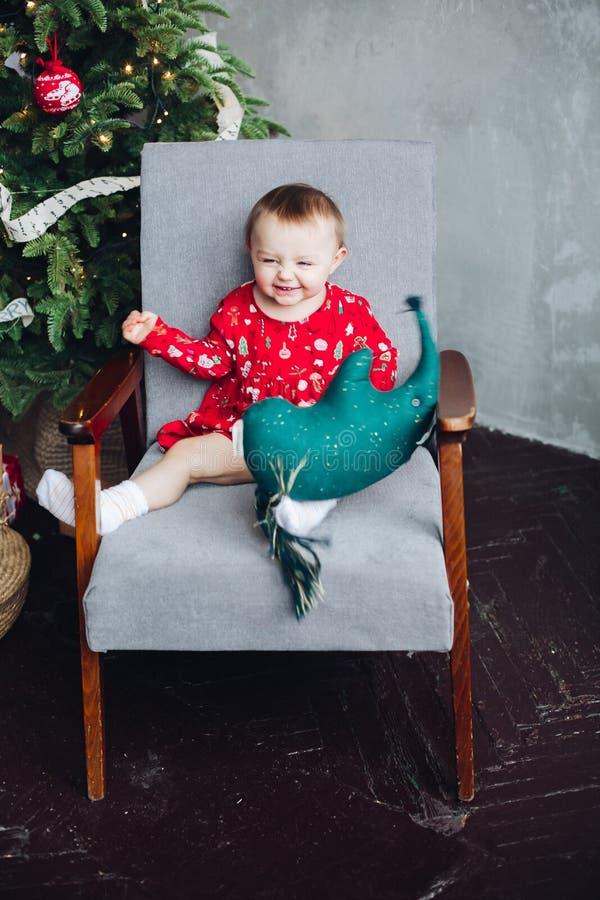 Uroczy dzieciak w czerwieni sukni z bożymi narodzeniami drukuje obsiadanie w krześle obrazy royalty free