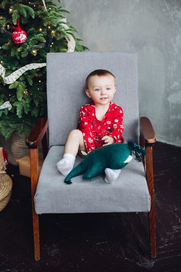 Uroczy dzieciak w czerwieni sukni z bożymi narodzeniami drukuje obsiadanie w krześle obraz stock