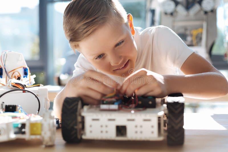 Uroczy dzieciaka naprawiania druty w mechanicznym pojazdzie fotografia royalty free