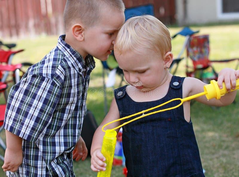 Uroczy dzieciaki dzieli sekrety fotografia stock