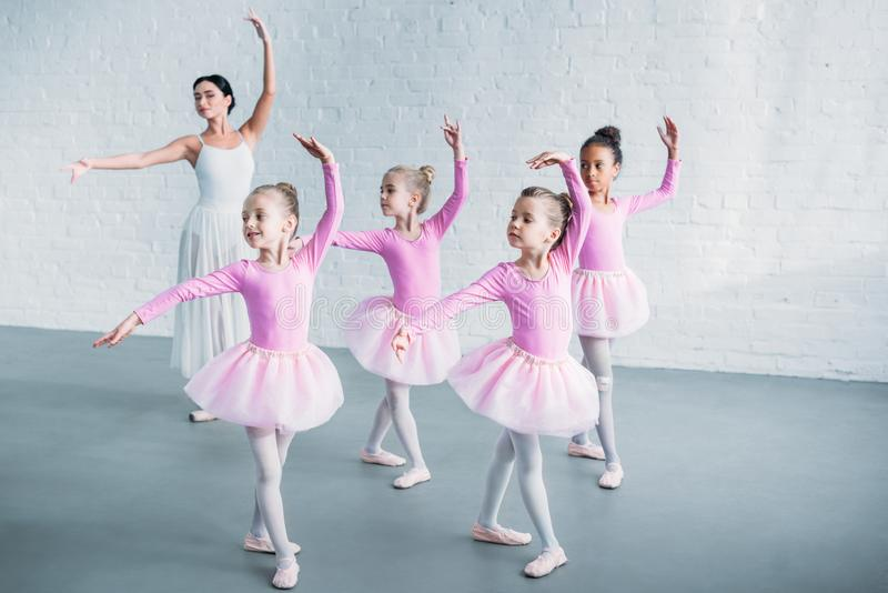 uroczy dzieciaki w różowym spódniczka baletnicy omijają ćwiczy balet z młodym nauczycielem obraz stock