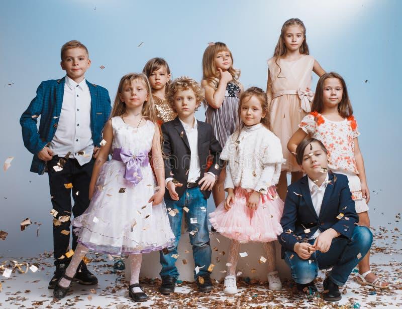 Uroczy dzieciaki zabawę wpólnie, rzutów colourful confetti, obraz royalty free