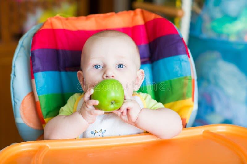 Uroczy dziecka łasowania jabłko w wysokim krześle zdjęcie stock