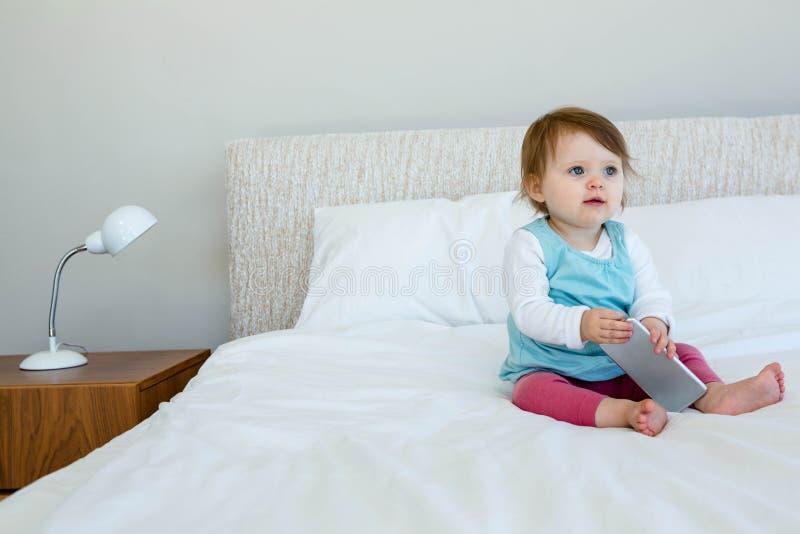 uroczy dziecka obsiadanie na łóżku obraz royalty free