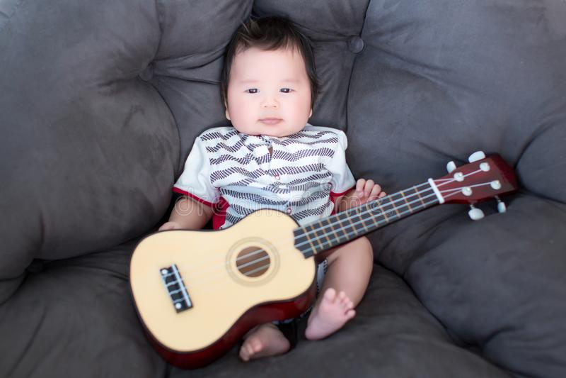 Uroczy dziecka obsiadanie na miękkiej kanapie z mini gitarą dziecko muzyk Praktyk muzyczne umiejętności dla dzieci muzyka i dziec obrazy royalty free