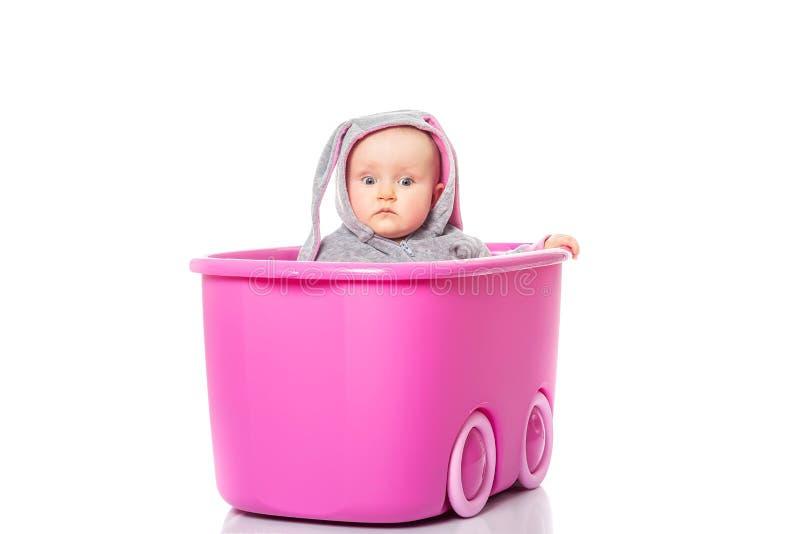 Uroczy dziecka obsiadanie w menchii pudełku, zakończenie w górę dziecka ` s gry fotografia stock
