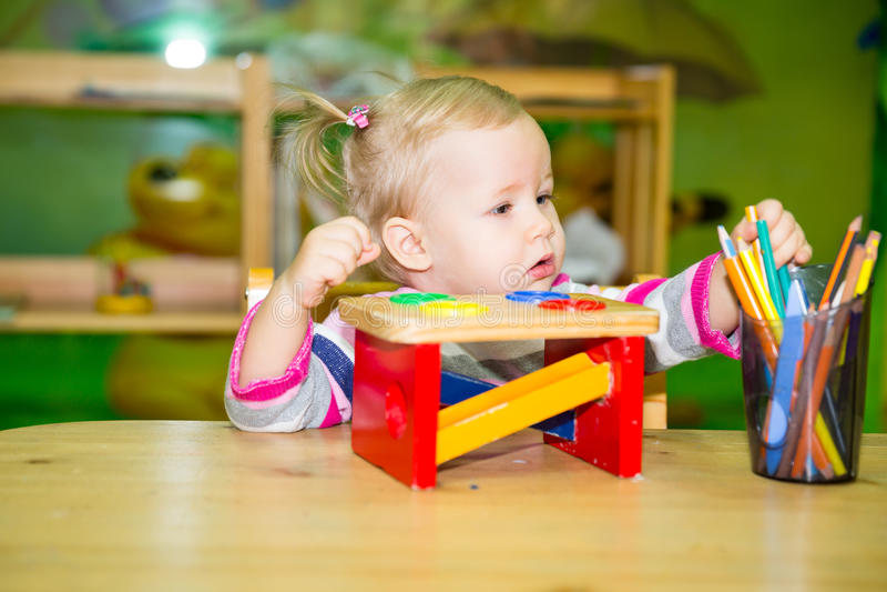 Uroczy dziecko dziewczyny rysunek z kolorowymi ołówkami w pepiniera pokoju Dzieciak w dziecinu w Montessori preschool klasie obrazy stock