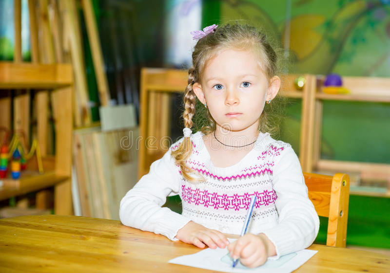 Uroczy dziecko dziewczyny rysunek z kolorowymi ołówkami w pepiniera pokoju Dzieciak w dziecinu w Montessori preschool klasie zdjęcie stock