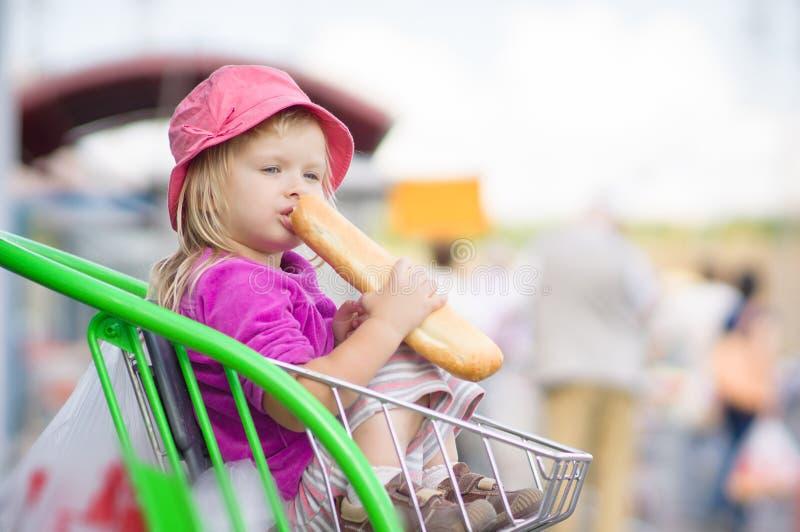 Uroczy dziecko je długiego chleb, siedzi w furze obraz royalty free