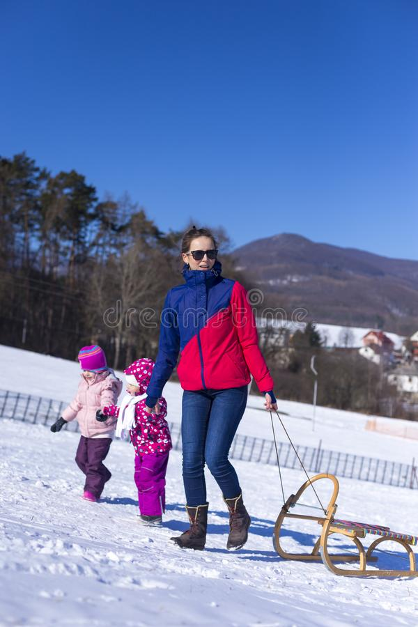 Uroczy dziecko jest usytuowanym w śniegu w białym śniegu w ciepłym kostiumu obrazy stock