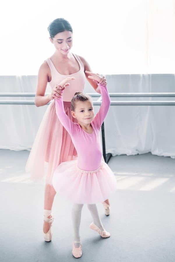 uroczy dziecko patrzeje kamerę w różowym spódniczka baletnicy podczas gdy trenujący z nauczycielem obraz stock
