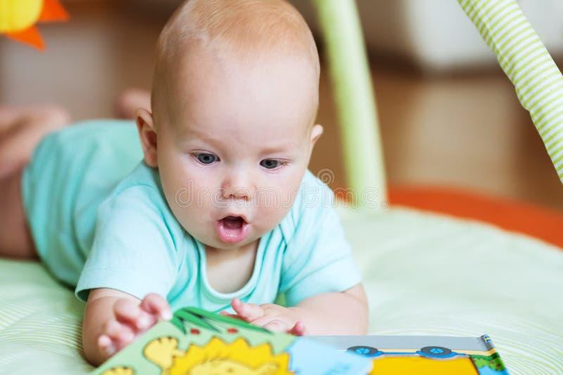 Uroczy dziecko patrzeje książkę obraz royalty free