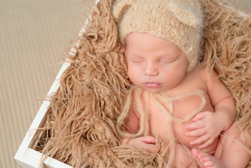 Uroczy dziecko w trykotowym kapeluszowym dosypianiu w drewnianym pudełku zdjęcie royalty free