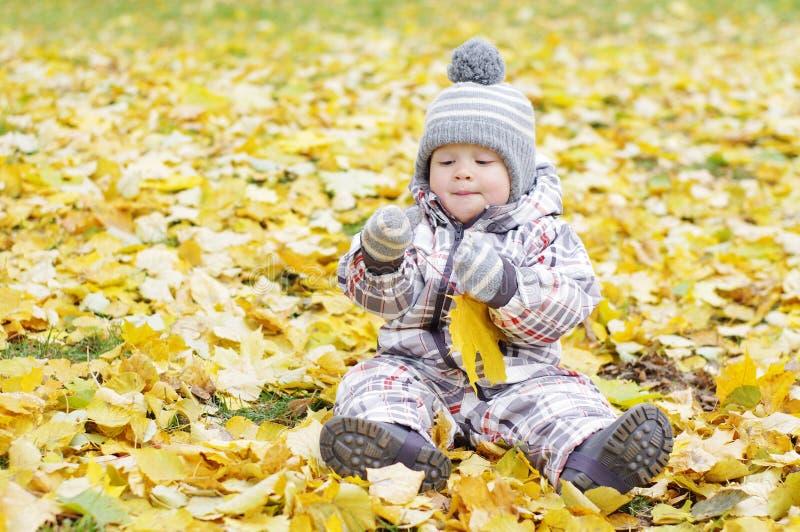Uroczy dziecko wiek 1 rok z żółtym liściem outdoors obraz stock