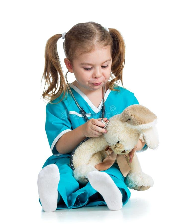 Uroczy dziecko z ubraniami doktorska egzamininuje zając zabawka nad wh fotografia royalty free
