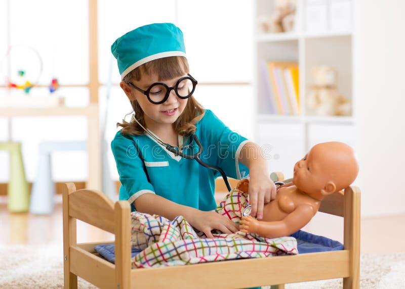 Uroczy dziecko z ubraniami doktorskie sztuki z lalą obraz royalty free
