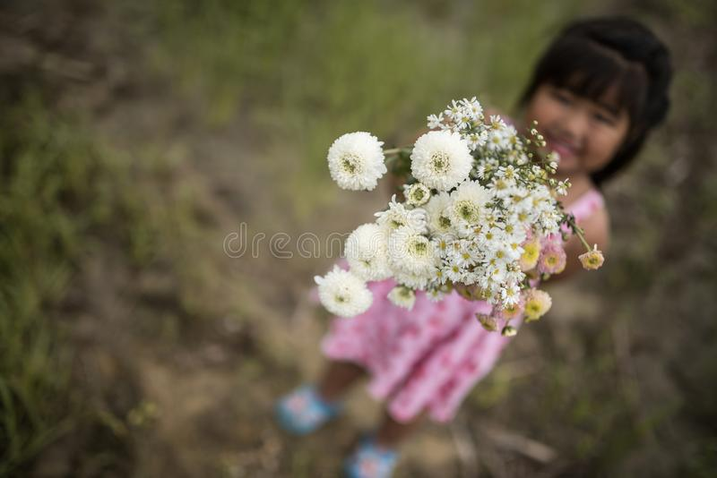 Uroczy dziewczyna dzieciak daje ci kwiaty z uśmiechniętą twarzą fotografia stock