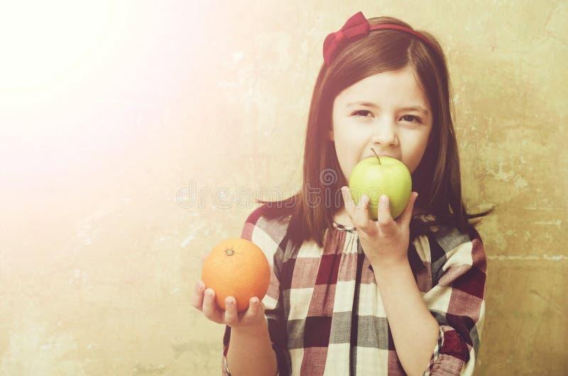 Uroczy dziewczyny ?asowania zieleni jab?ko z pomara?cze w r?ce obraz royalty free