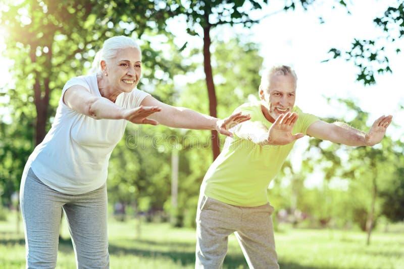 Uroczy emeryci zgina i rozciąga przy ich szkoleniem fotografia royalty free