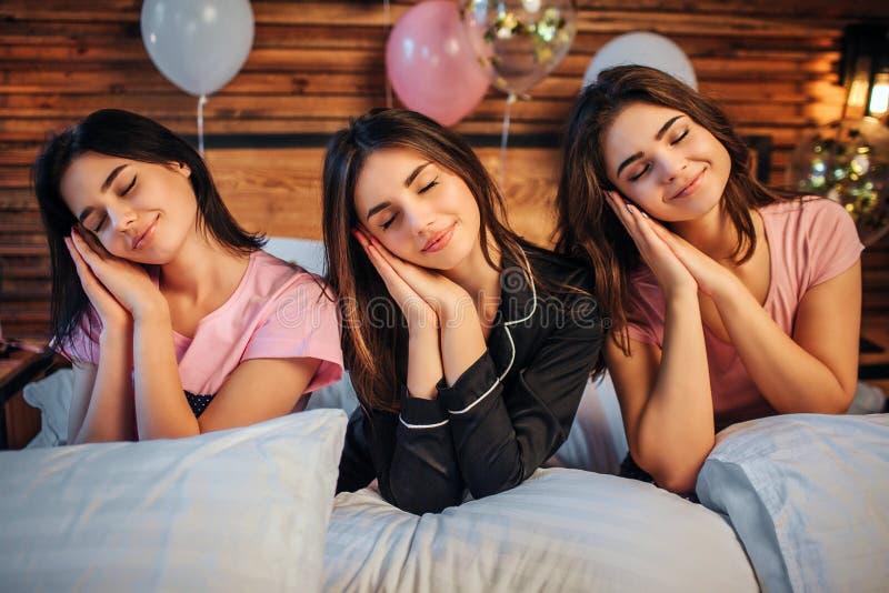 Uroczy młodzi modele siedzą na łóżku w pokoju Są ubranym piżamy Dziewczyna chwyta głowy na rękach i utrzymaniu przyglądają się za fotografia royalty free