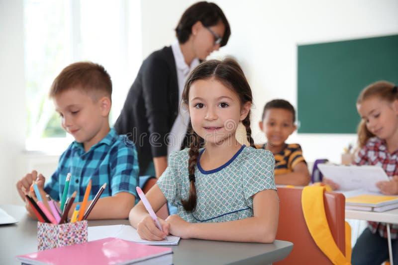 Uroczy małe dzieci siedzi przy biurkami w sala lekcyjnej fotografia royalty free