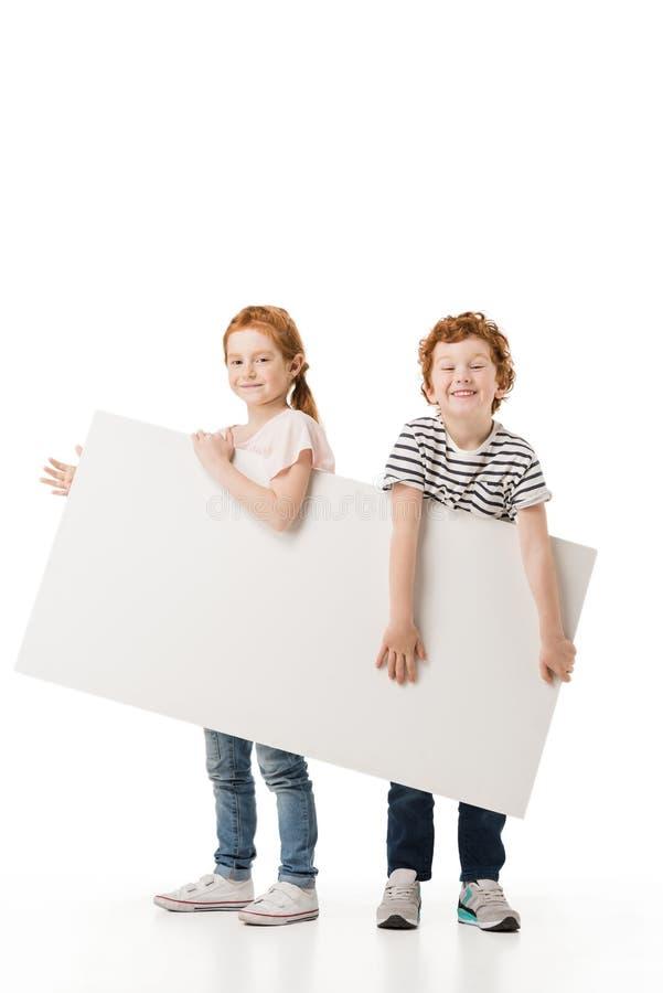 uroczy małe dzieci trzyma pustego plakat i ono uśmiecha się przy kamerą obrazy royalty free