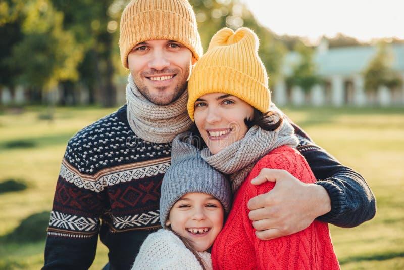 Uroczy małe dziecko stojak blisko do jej czule rodziców, cieszy się wydający czas wpólnie, obejmuje each inny, uśmiech szczęśliwi obraz royalty free