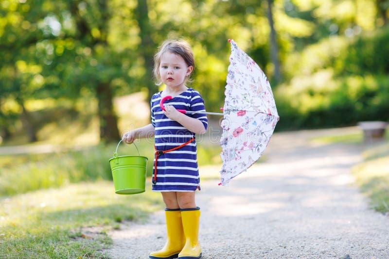 Uroczy małe dziecko w żółtych podeszczowych butach i parasolu w summe obraz stock
