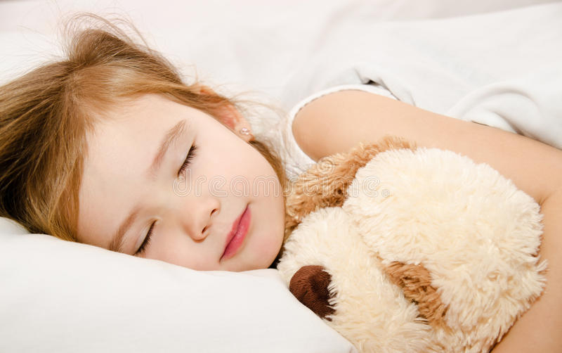 Uroczy małej dziewczynki dosypianie w łóżku zdjęcia stock