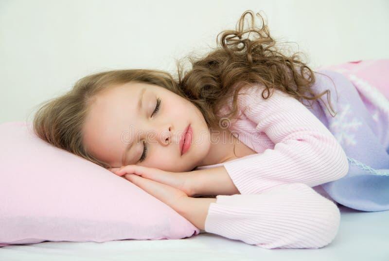Uroczy małej dziewczynki dosypianie w jej łóżku obrazy royalty free