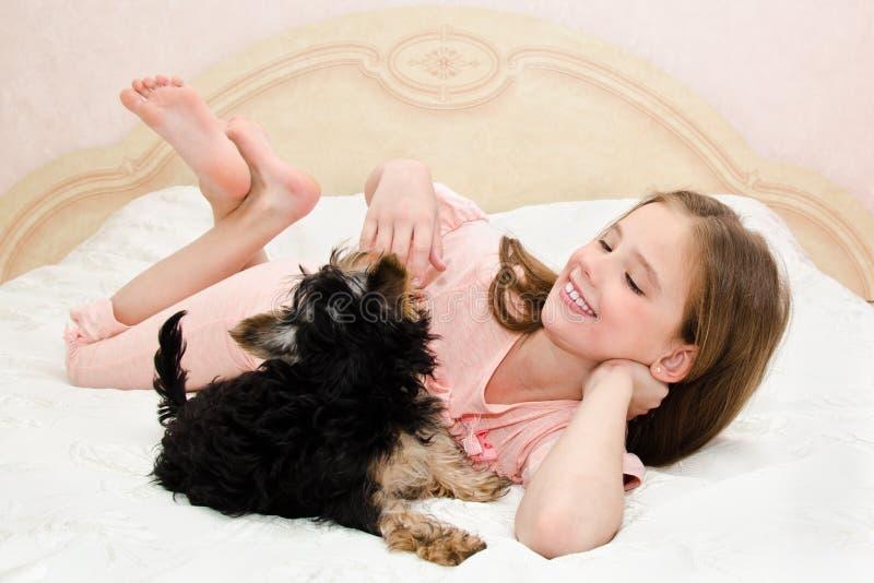 Uroczy małej dziewczynki dziecka mienie i bawić się z szczeniaka yorksh obraz royalty free