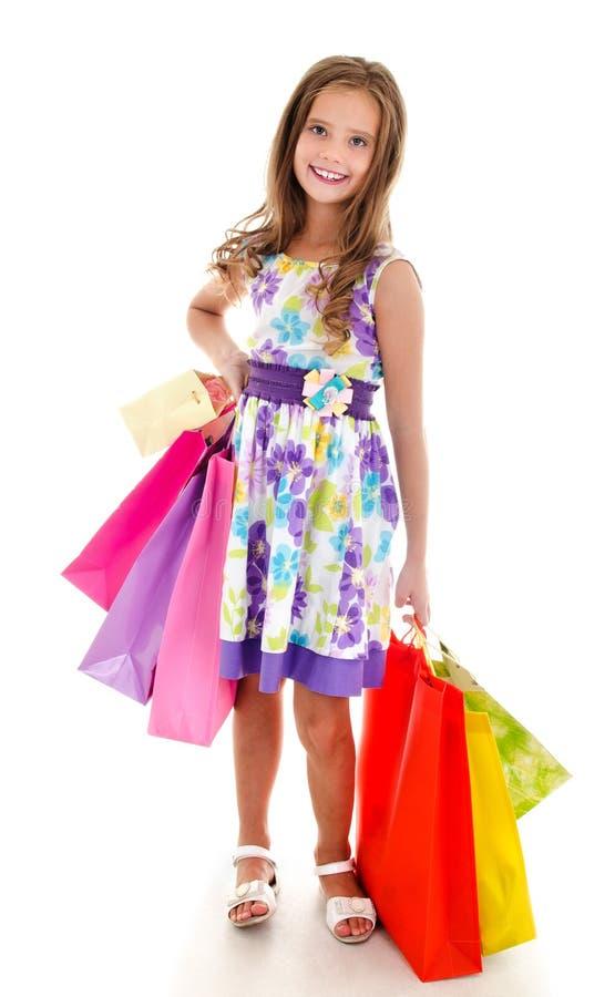 Uroczy małej dziewczynki dziecka mienie robi zakupy kolorowe papierowe torby obraz royalty free