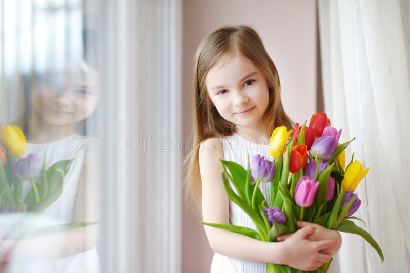 Uroczy małej dziewczynki mienia tulipany okno fotografia royalty free