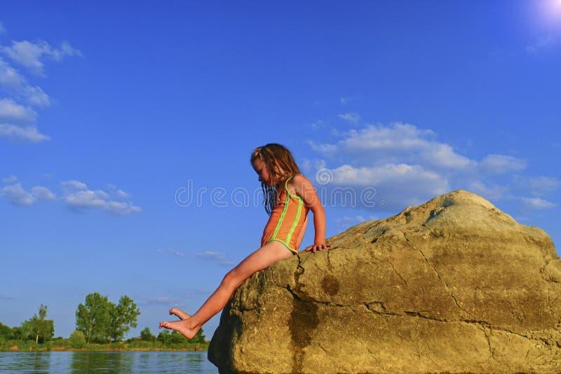 Uroczy małej dziewczynki obsiadanie na dużym kamieniu w jeziorze na gorącym letnim dniu Dziecko ubierający w swimsuit Mała dziewc fotografia stock