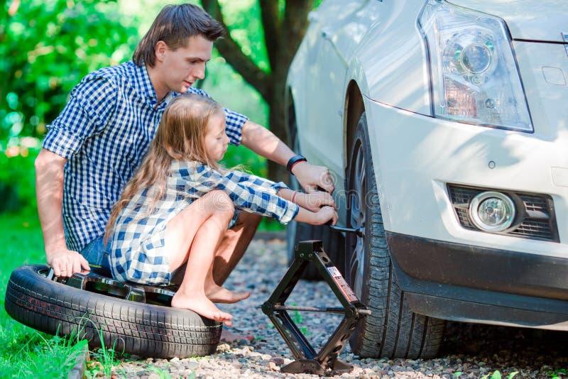 Uroczy małej dziewczynki obsiadanie na oponie zmieniać samochodowego koło outdoors na pięknym letnim dniu pomaga ojcu i zdjęcie royalty free