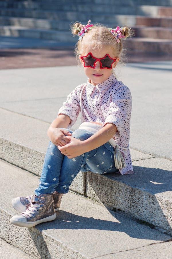 Uroczy małej dziewczynki obsiadanie na schodkach fotografia royalty free