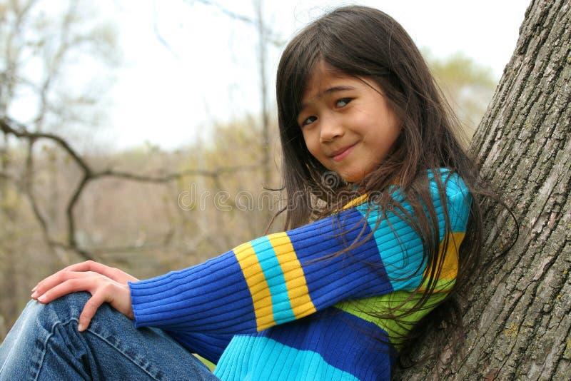 Uroczy małej dziewczynki obsiadanie w drzewie zdjęcie royalty free